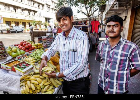 Mumbai India Asian Apollo Bandar Colaba Indumati Sakharkar Marg Causeway Market shopping man sidewalk vendor fruit - Stock Photo