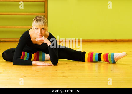 Ballet dancer doing stretching exercise on a floor - Stock Photo