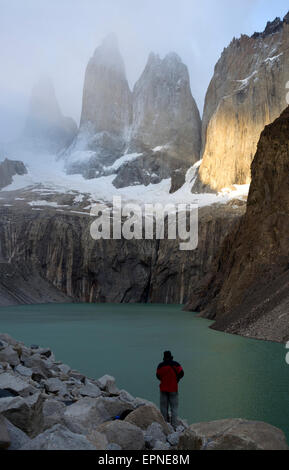 Trekker contemplating Torres del Paine. Base of the Towers. Torres del Paine National Park. Patagonia. Chile - Stock Photo