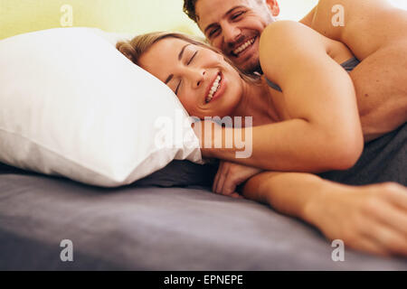 Happy young couple embracing while lying next to each other on bed. Caucasian couple smiling in bed together. Couple - Stock Photo