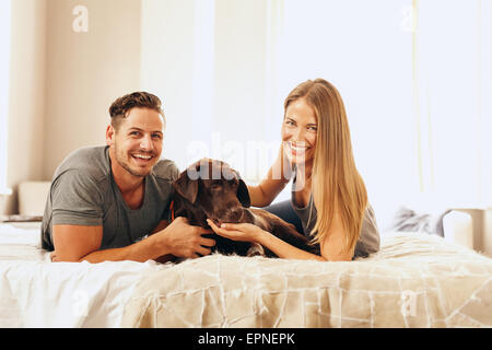 Shot of a young couple lying on the bed with their dog. Cheerful man and woman looking at camera with their pet - Stock Photo