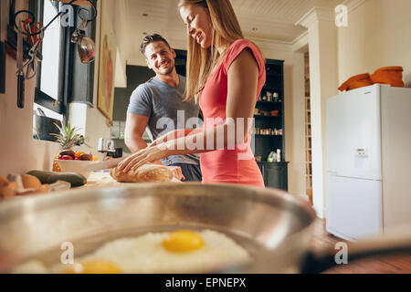 Indoor shot of happy young couple standing at the kitchen counter in morning. Woman cutting bread for breakfast. - Stock Photo