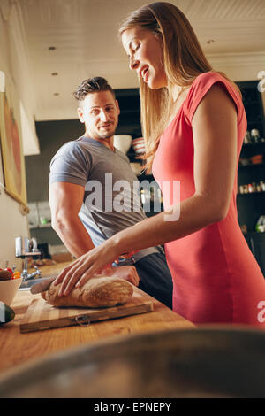 Shot of young couple standing in kitchen. Young woman cutting bread with man standing by. Focus on woman preparing - Stock Photo