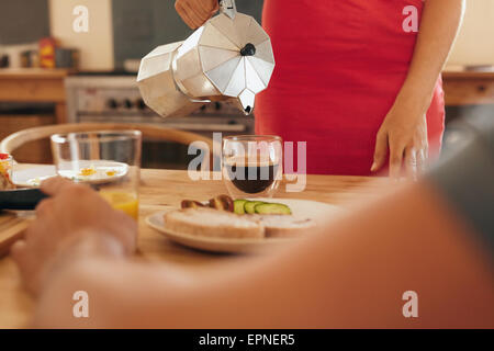 Cropped shot of woman serving black coffee in small glass on breakfast table. Pouring fresh coffee from a jug into - Stock Photo