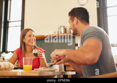 Shot of cheerful young couple having breakfast in kitchen at home. Young woman drinking coffee looking at man smiling - Stock Photo