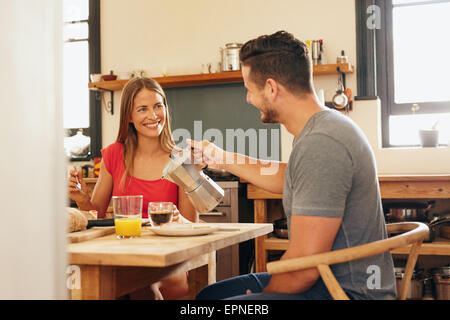 Indoor shot of young man serving coffee to his girlfriend having breakfast in kitchen at home. Smiling young couple - Stock Photo