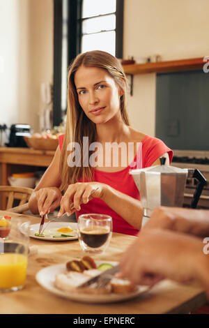 Portrait of attractive young woman sitting at breakfast table eating and looking at camera. Caucasian female having - Stock Photo