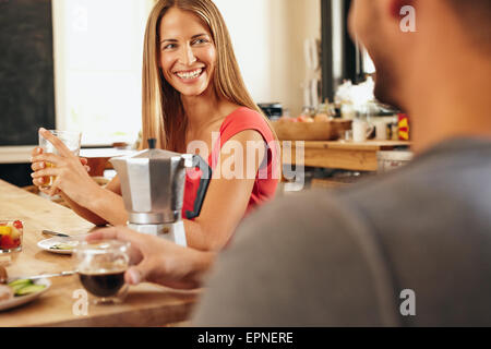 Happy young couple sitting together in the kitchen and having breakfast. Smiling young woman talking with her boyfriend - Stock Photo