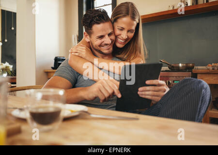 Couple smiling as they read a tablet computer together in morning in the kitchen. Young man and woman catching up - Stock Photo