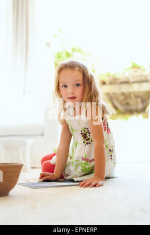 Portrait of cute little girl drawing while sitting on floor at home looking at camera. Elementary age young girl - Stock Photo