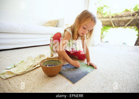 Shot of innocent little caucasian girl sitting on floor coloring a picture with color chalks. Schoolgirl drawing - Stock Photo