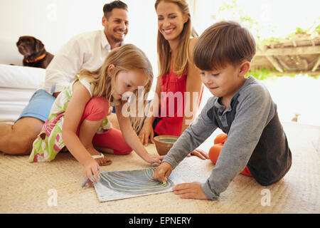 Little boy and girl drawing with chalk colors while sitting on floor. Children drawing with their parents in living - Stock Photo