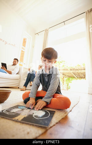 Little schoolboy sitting on floor drawing with his parents sitting in background on couch. Family in living room. - Stock Photo