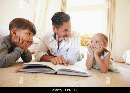 Indoor shot of young man with two kids reading a story book. Family lying on the floor with a book in living room. - Stock Photo