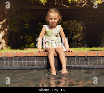 Adorable little girl enjoying sitting by edge of pool on sunny day. Young girl with her feet in swimming pool looking - Stock Photo