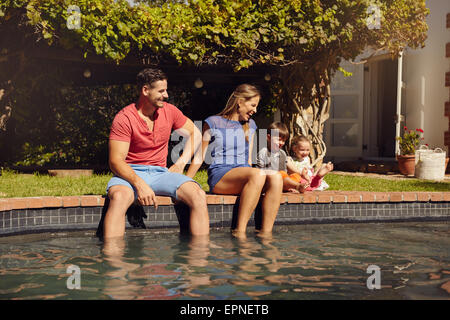 Happy young couple sitting on the edge of swimming pool with their kids enjoying a hot summer day near pool. Couple's - Stock Photo