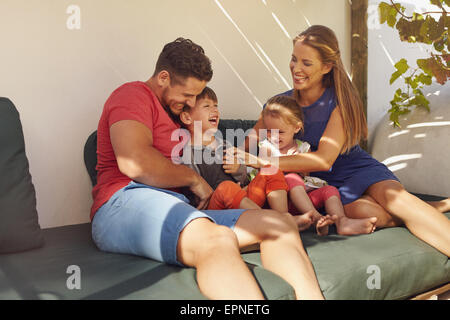 Shot of happy family of four in their backyard having fun, sitting on couch playing. Parents playing with kids laughing - Stock Photo