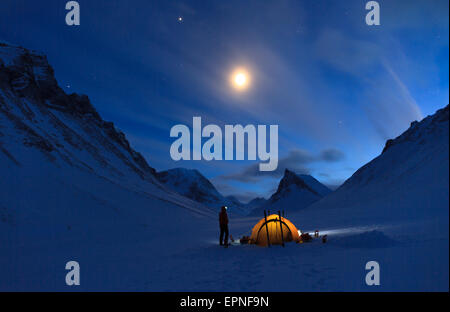 Winter campsite with yellow tent in the mountains of Swedish Lapland. - Stock Photo