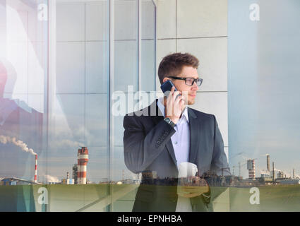 double exposure of urban attractive businessman with phone device and industrial enterprise building background - Stock Photo