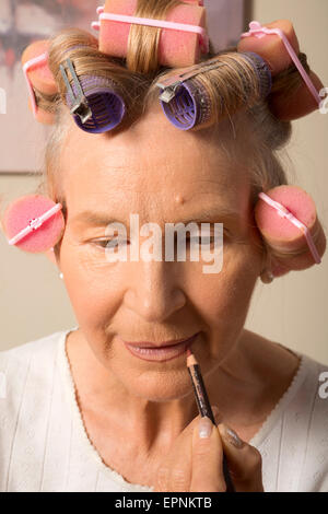 Woman in curlers applying lipliner - Stock Photo