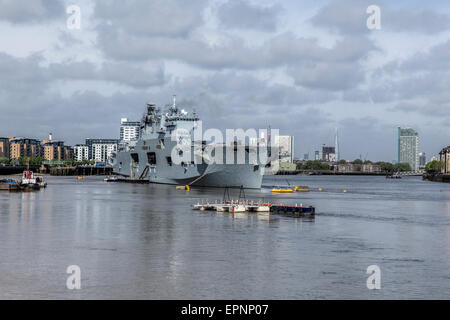 Royal Navy helicopter carrier ship HMS Ocean on the River Thames in Greenwich London with the City of London and - Stock Photo