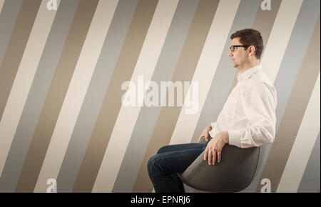 Portrait of pensive man sitting and waiting on chair in corridor. - Stock Photo