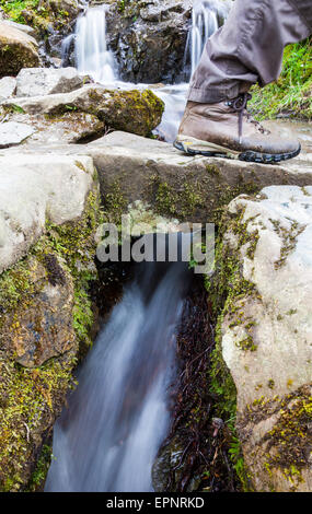 A walker's foot crossing a small bridge on the public footpath alongside Aira Beck, near Aira Force, lake District, - Stock Photo