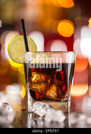 Glass of cola drink on bar counter with ice cubes - Stock Photo
