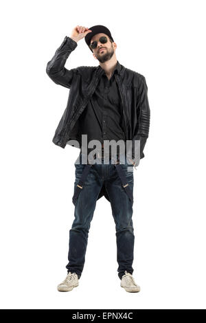 Young bearded man holding cap wearing sunglasses looking at camera. Full body length portrait isolated over white - Stock Photo