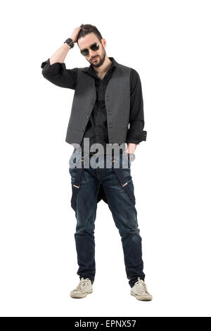 Serious young bearded man running fingers through hair looking at camera. Full body length portrait isolated over - Stock Photo