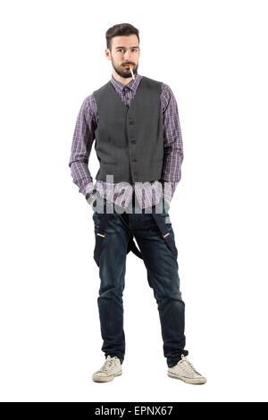 Young serious hipster looking at camera with cigarette in his mouth. Full body length portrait isolated over white - Stock Photo