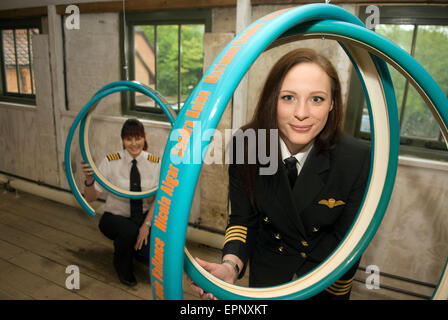 Two female airline pilots looking through artist Ros Burgin's 12-piece installation 'Skylines' intended to celebrate - Stock Photo