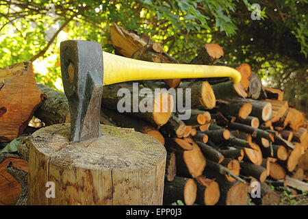 An old axe stuck in log with chopped wood - Stock Photo