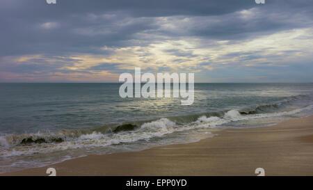 Dusk settles over a calm Arabian Sea and also the deserted, peaceful sandy beach at Thottada Village near Kannur, - Stock Photo