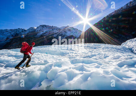 A guide with his ice axe walks up the ice on Fox Glacier in the Southern Alps of New Zealand - Stock Photo