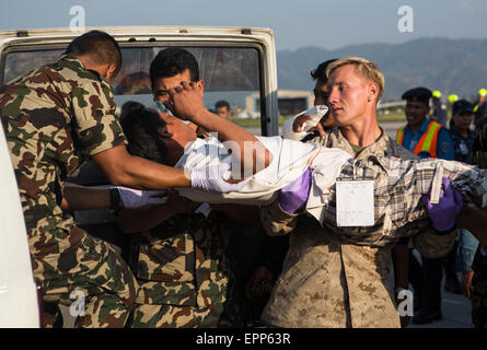 U.S. service members from Joint Task Force 505 and Nepalese army doctors treat victims at a medical triage area - Stock Photo