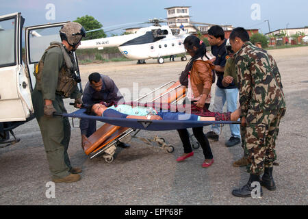 U.S. service members from Joint Task Force 505 and Nepalese soldiers move a victim onto an ambulance at Tribhuvan - Stock Photo