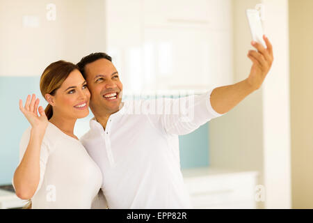 portrait of happy couple taking selfie together at home - Stock Photo