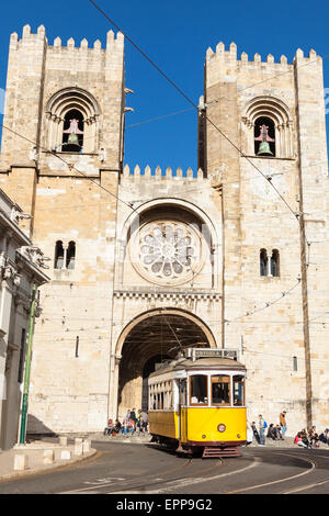 Famous yellow 28 tramway  of Lisbon passing in front of Santa Maria cathedral in Portugal - Stock Photo