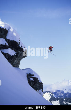 Man launching a cliff on his skis in Champery, Switzerland - Stock Photo