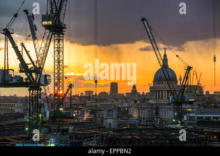 Cityscape of silhouetted tower cranes on the Bloomberg Place construction site, London EC4, skyline in setting sun - Stock Photo