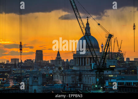 Cityscape of silhouetted cranes on the Bloomberg Place construction site, London EC4, in setting sun with St Paul's - Stock Photo