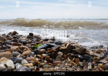 Gentle waves rolling onto pebbly beach - Stock Photo