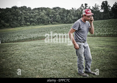 A man talks on his cell phone out in the field of their family farm in Keymar, Maryland. - Stock Photo