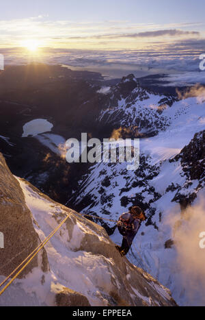 A climber rappels down Cerro Torre's south east ridge at dawn, after an ascent of that peak, in Argentine Patagonia - Stock Photo