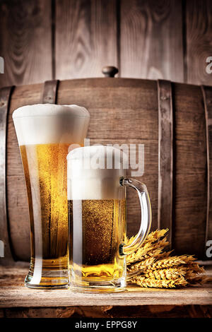 Tall glass and a mug of light beer on a background of the old wooden barrels - Stock Photo
