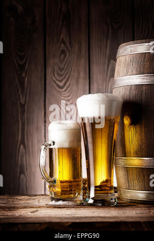 Tall glass and mug beer on the background of wooden barrels - Stock Photo