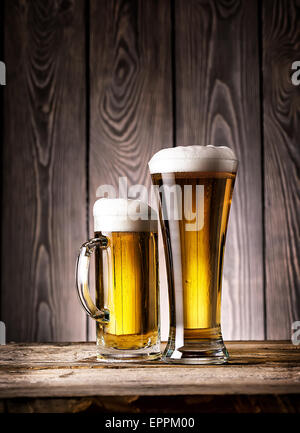 Tall glass and mug of light beer with foam on wooden background - Stock Photo
