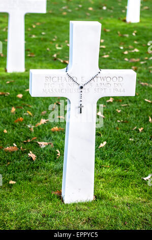 A rosary-draped white cross markes the burial site of one of the 9,387 war dead in the American Cemetery, Omaha - Stock Photo