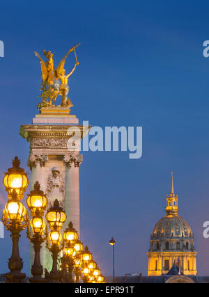 Row of lampposts along Pont Alexandre III with dome of Hotel des Invalides beyond, Paris, France - Stock Photo
